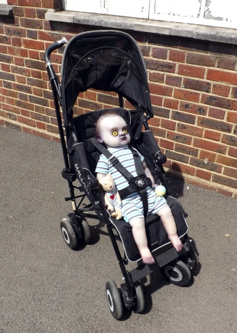 Finished and dressed full body changeling baby prop in push chair